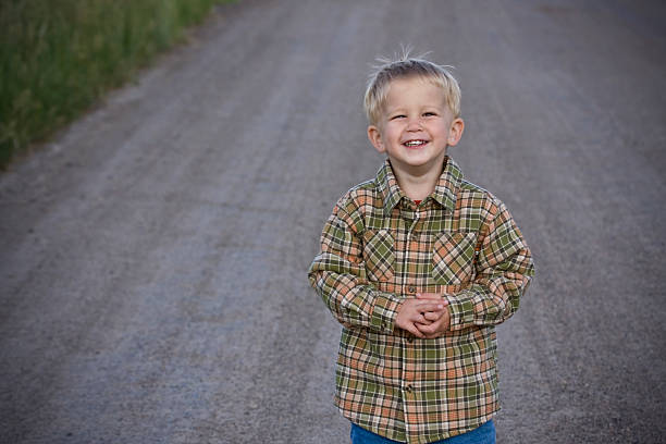 boy on the road young boy smiles while standing on a gravel roadMore Animals! middle of the road stock pictures, royalty-free photos & images