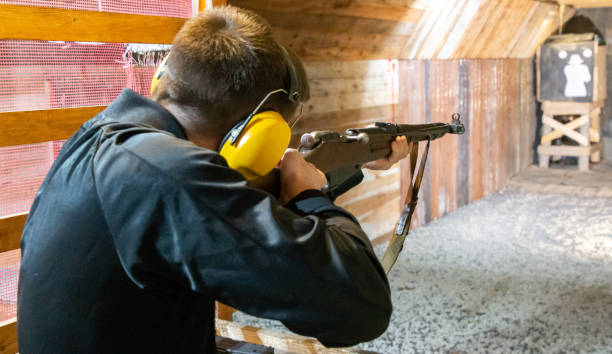 boy on the shooting range aiming an old rifle at the target stock photo
