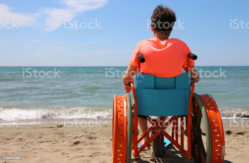 boy on the special wheelchair with metal wheels on the beach stock photo