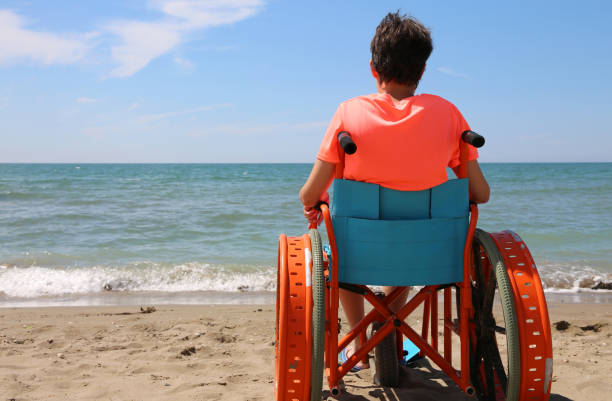 boy on the special wheelchair with metal wheels on the beach boy on the special wheelchair with metal wheels on the beach by the sea als stock pictures, royalty-free photos & images