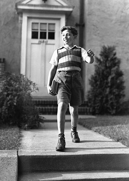 Boy (10-11) on way to school, (B&W)  early 20th century stock pictures, royalty-free photos & images