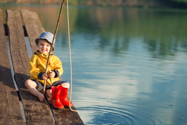 Boy on wooden dock with a fishing net stock photo