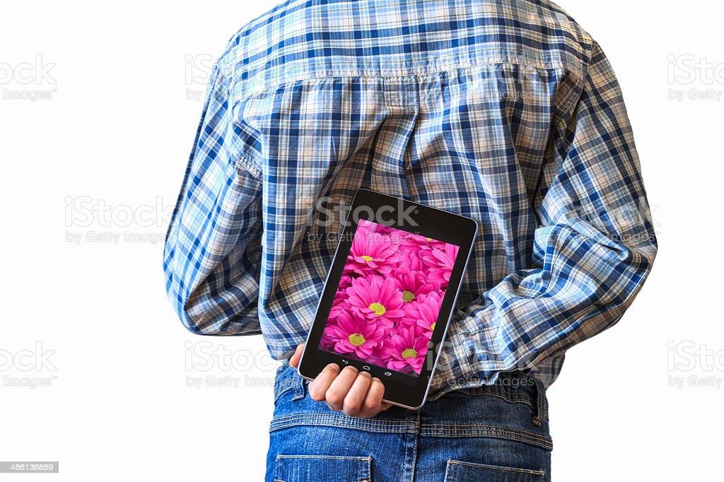 Boy or man hiding chrysanthemum screen tablet computer behind back royalty-free stock photo