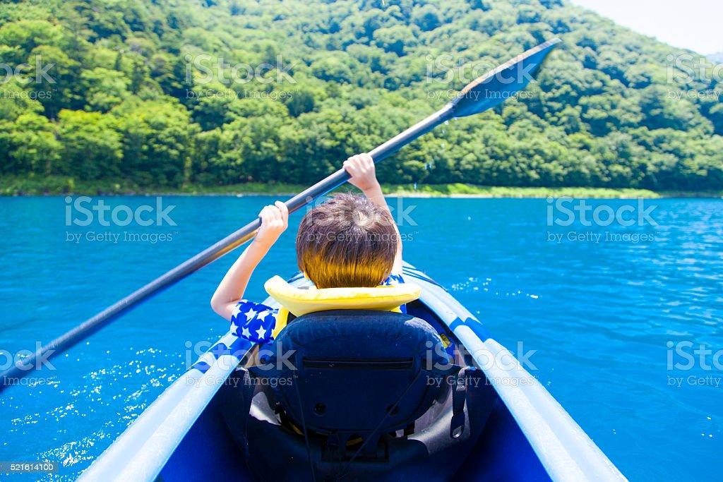 Boy paddling on kayak stock photo