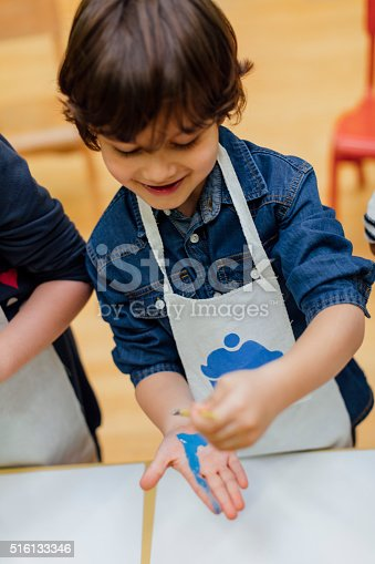 istock Boy Painting His Hand With Watercolors 516133346