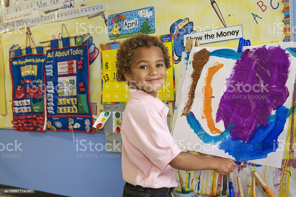 Boy (4-5) painting on easel, smiling, portrait 免版稅 stock photo