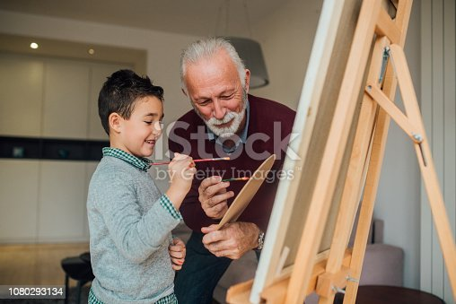 istock Boy painting with grandfather 1080293134