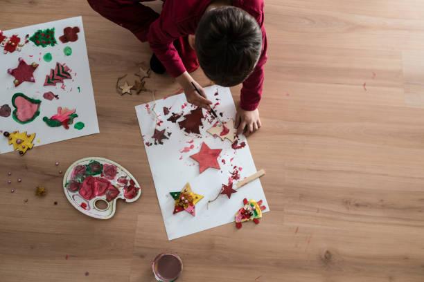 junge malerei weihnachten kunsthandwerk aus holz - basteln mit kindern weihnachten stock-fotos und bilder