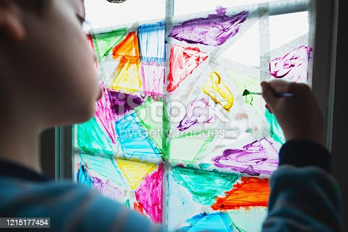 Painting a stained glass pattern on a window pane during the Stay at Home order.