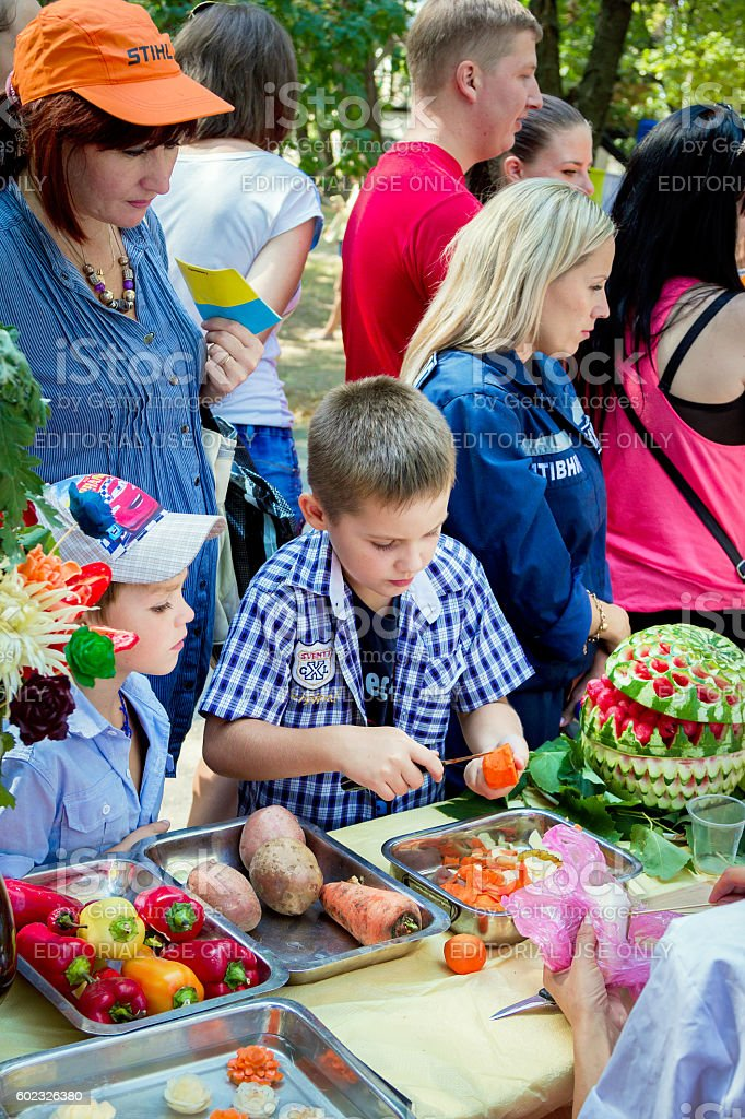 Boy participating at fruits and vegetables carving workshop - Photo