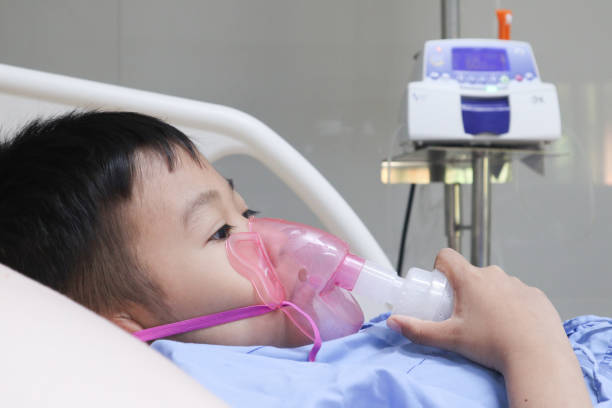 Boy patient with asthma allergy using the asthma inhaler.Inhaler mask for treatment in hospital.Health asthmatic in hospital.healthcare and medical concept stock photo