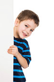 Smiling boy peek out from vertical empty banner, isolated on white