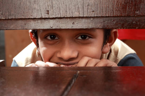 Boy peek through a gap stock photo