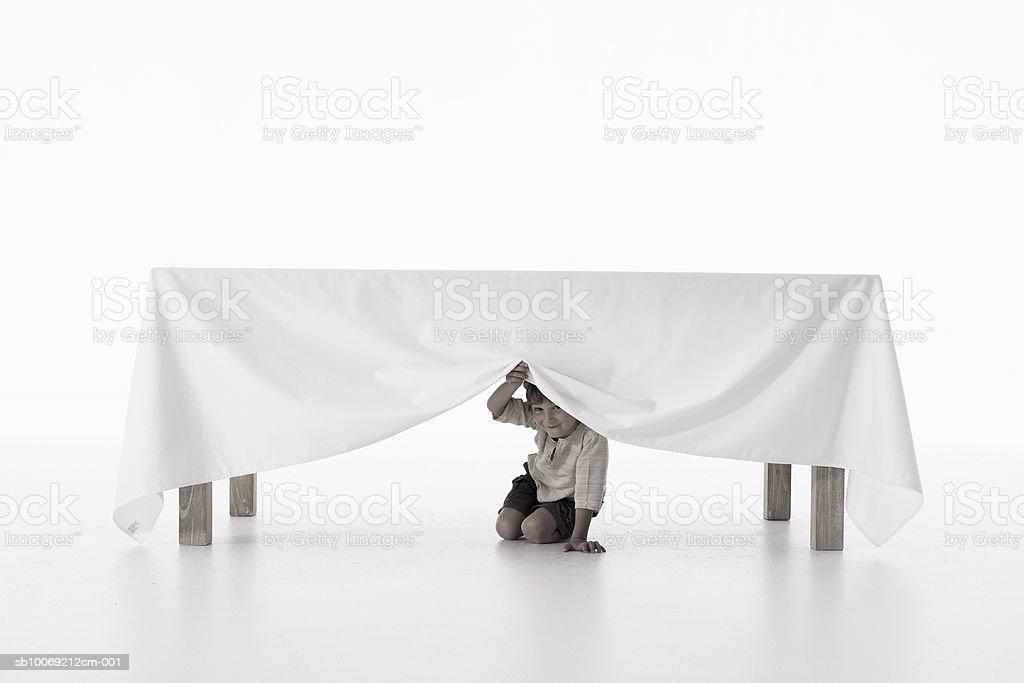 Menino (4-5 anos) caminho de menos de toalha de mesa, Foto de estúdio, port foto royalty-free