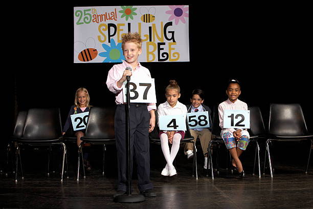 Boy (8-9) performing at spelling bee competition stock photo