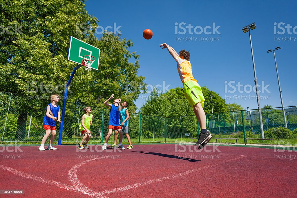 Boy performs foul shot at basketball game stock photo