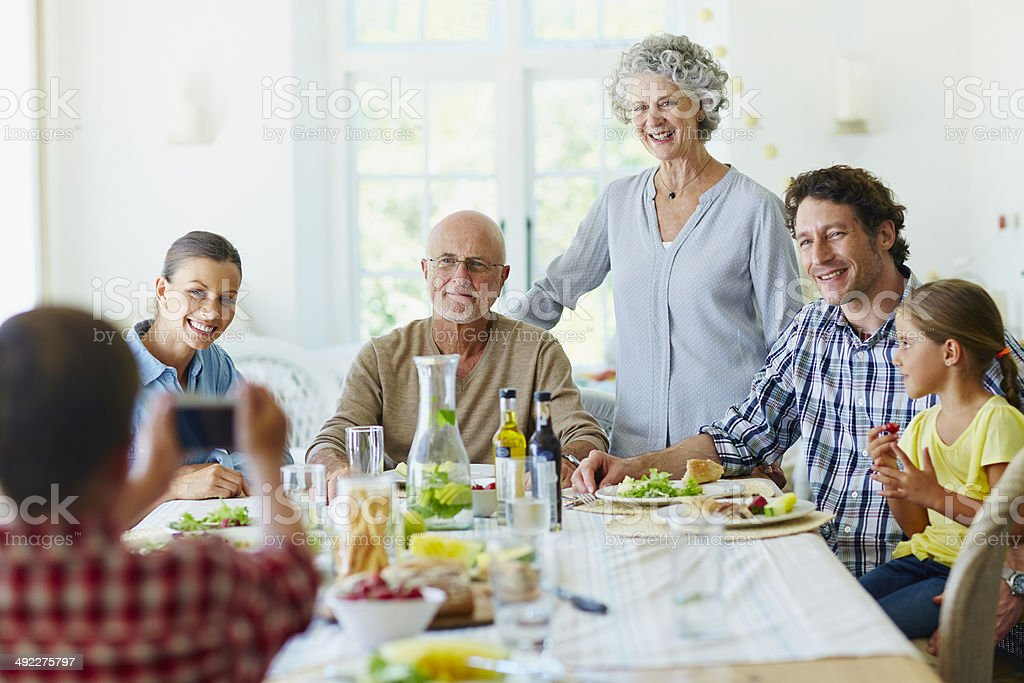 Boy photographing family at dining table stock photo