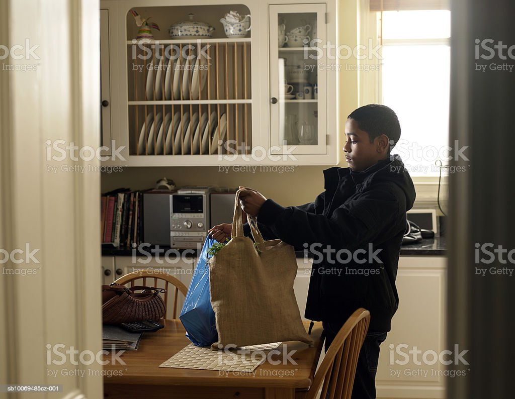 Boy (12-13) placing shopping bags on kitchen table royalty free stockfoto
