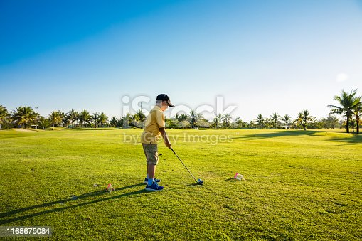boy play golf in green course in Thailand