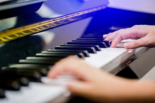 Boy play the piano with selective focus to piano key and hands.