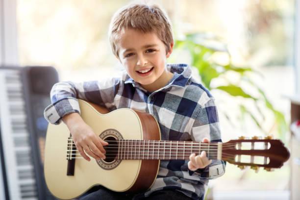 jungen spielen akustikgitarre - one song training stock-fotos und bilder