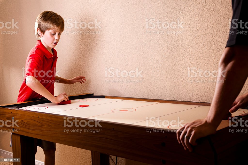 Boy playing air hockey with dad stock photo