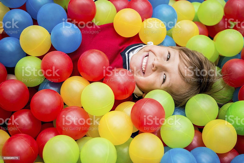 Boy playing at a ball pool stock photo