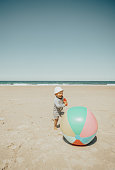 Boy playing at the beach with ball