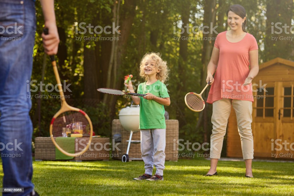 Boy playing badminton with parents - foto de acervo