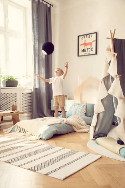 junge ballspielen im schlafzimmer innenraum mit teppich und zelt neben blauen bett und fox poster. echtes foto - fuchs kissen stock-fotos und bilder