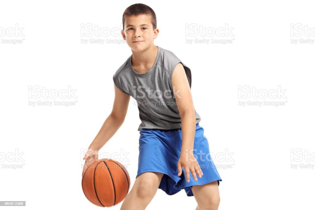 Boy playing basketball isolated on white background