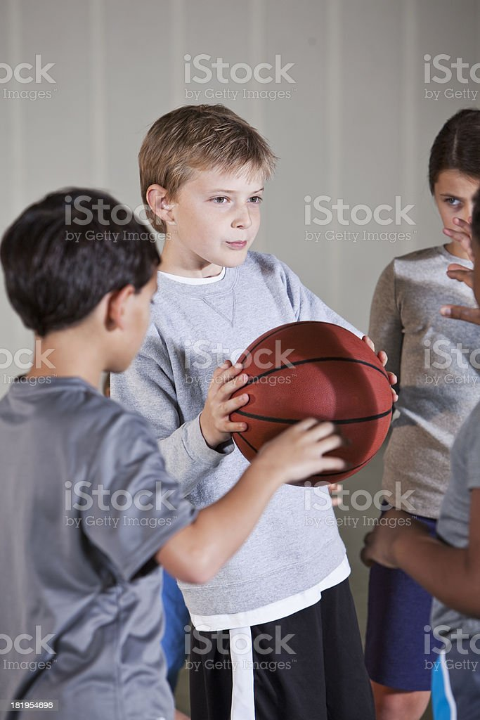 Boy playing basketball with friends stock photo