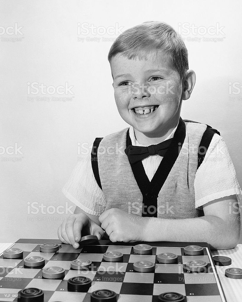 Boy playing checkers 免版稅 stock photo