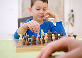 Portrait of cheerful little child playing chess with parents at home