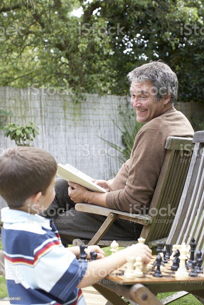 Boy playing chess in backyard stock photo