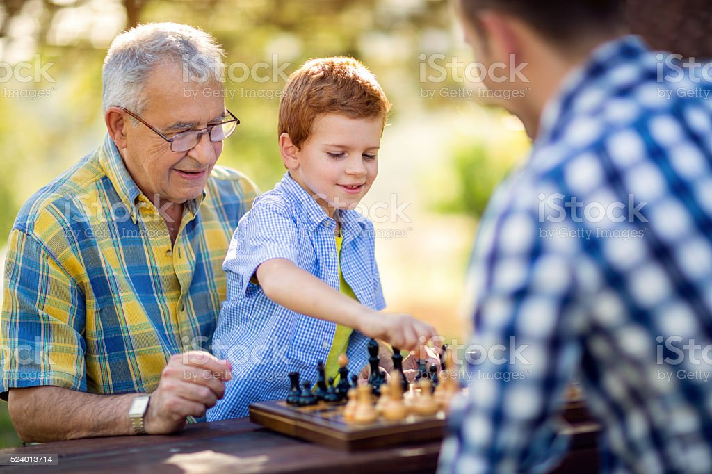 boy playing chess on the table stock photo