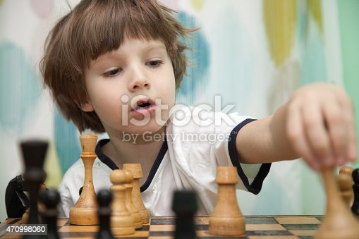 Portrait of a little boy playing chess