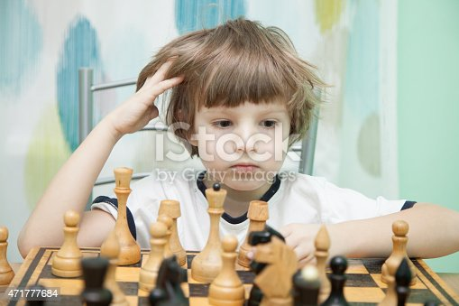 Portrait of a Young boy thinking on chess
