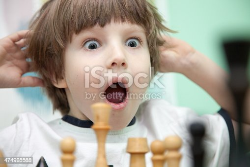 Portrait of a little boy thinking over chess