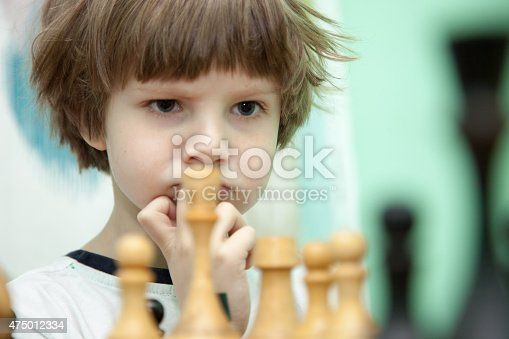 Closeup portrait of a school boy playing chess