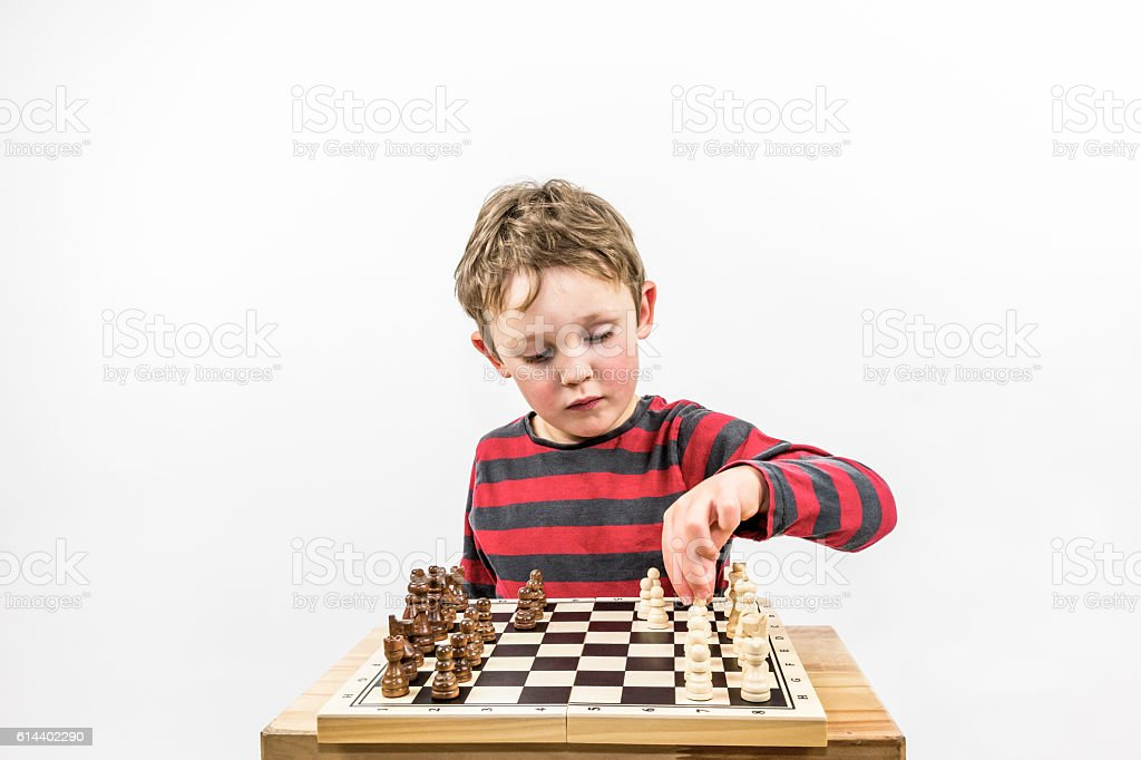 Boy playing chess with himself, portrait studio shot. stock photo