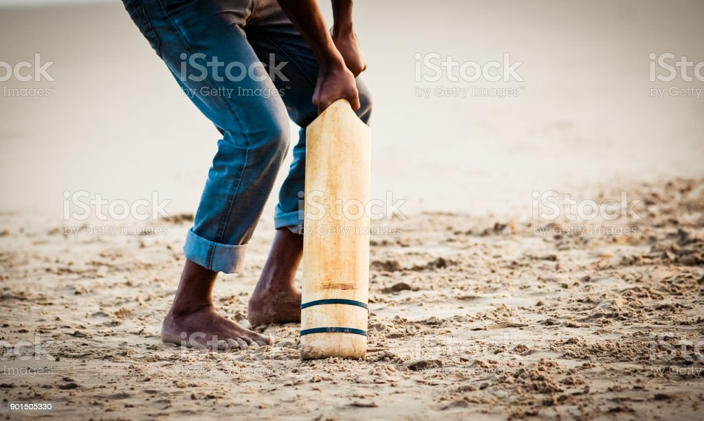 boy playing cricket at sunset on tropical beach in Sri Lanka stock photo