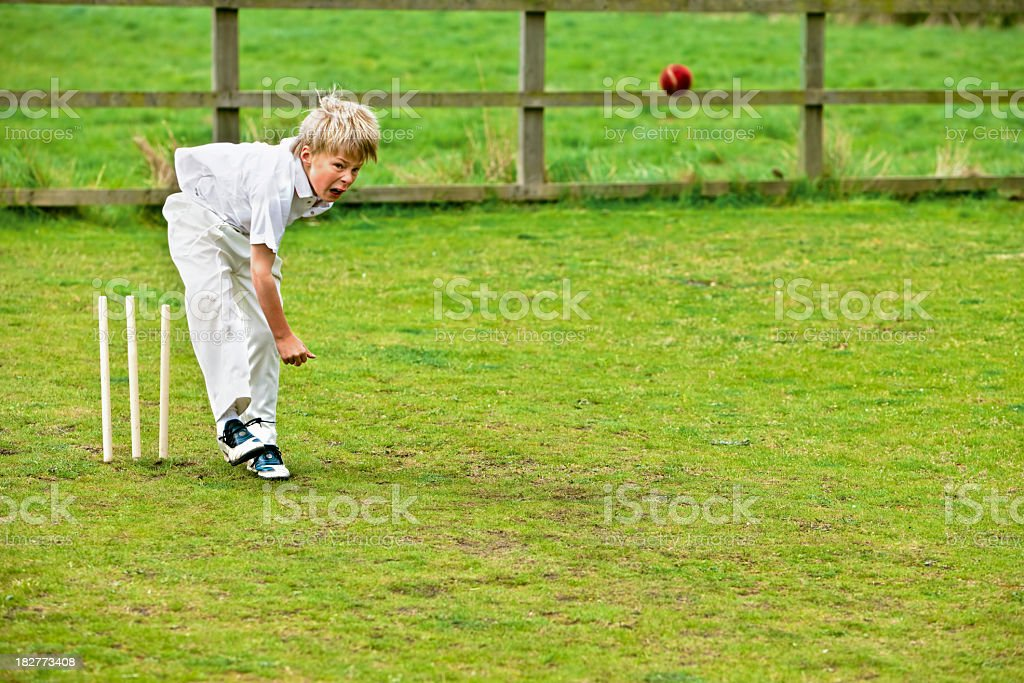 boy playing cricket with bowling action on grass stock photo