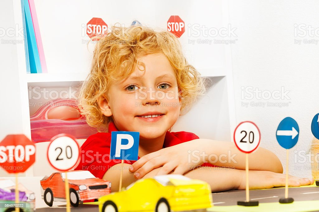 Boy playing driver with toy cars and road signs stock photo
