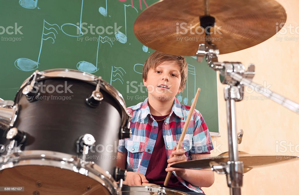 Boy playing drums at music class stock photo