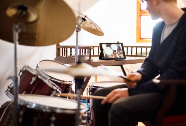 Boy playing drums during an online class at home stock photo