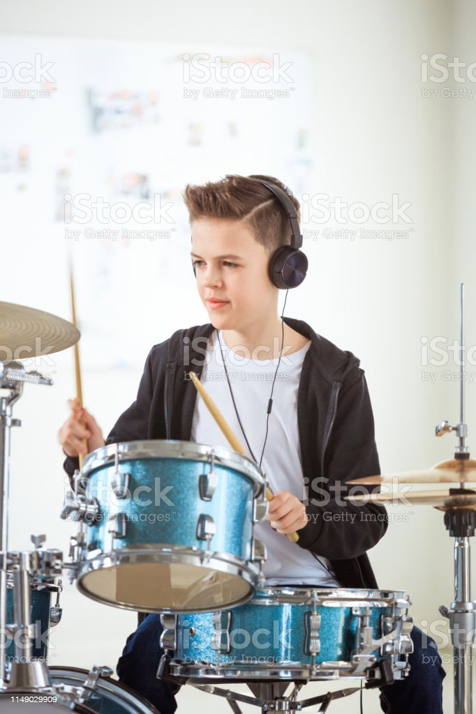 Boy playing drums while listening music in class Pre-adolescent boy practicing drums while listening music. Student is playing percussion instrument in training class. He is wearing headphones at education building. 12-13 Years Stock Photo