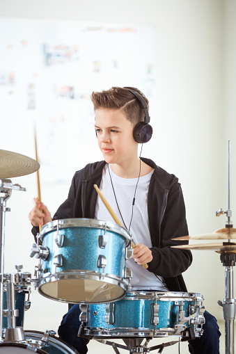 Boy Playing Drums While Listening Music In Class Stock Photo - Download Image Now