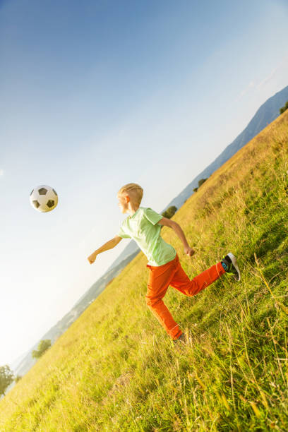 Boy playing football in a meadow, having fun stock photo