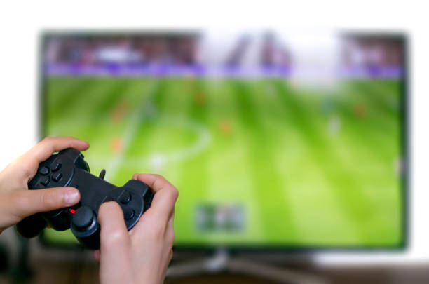 boy playing football on television screen with game console stock photo